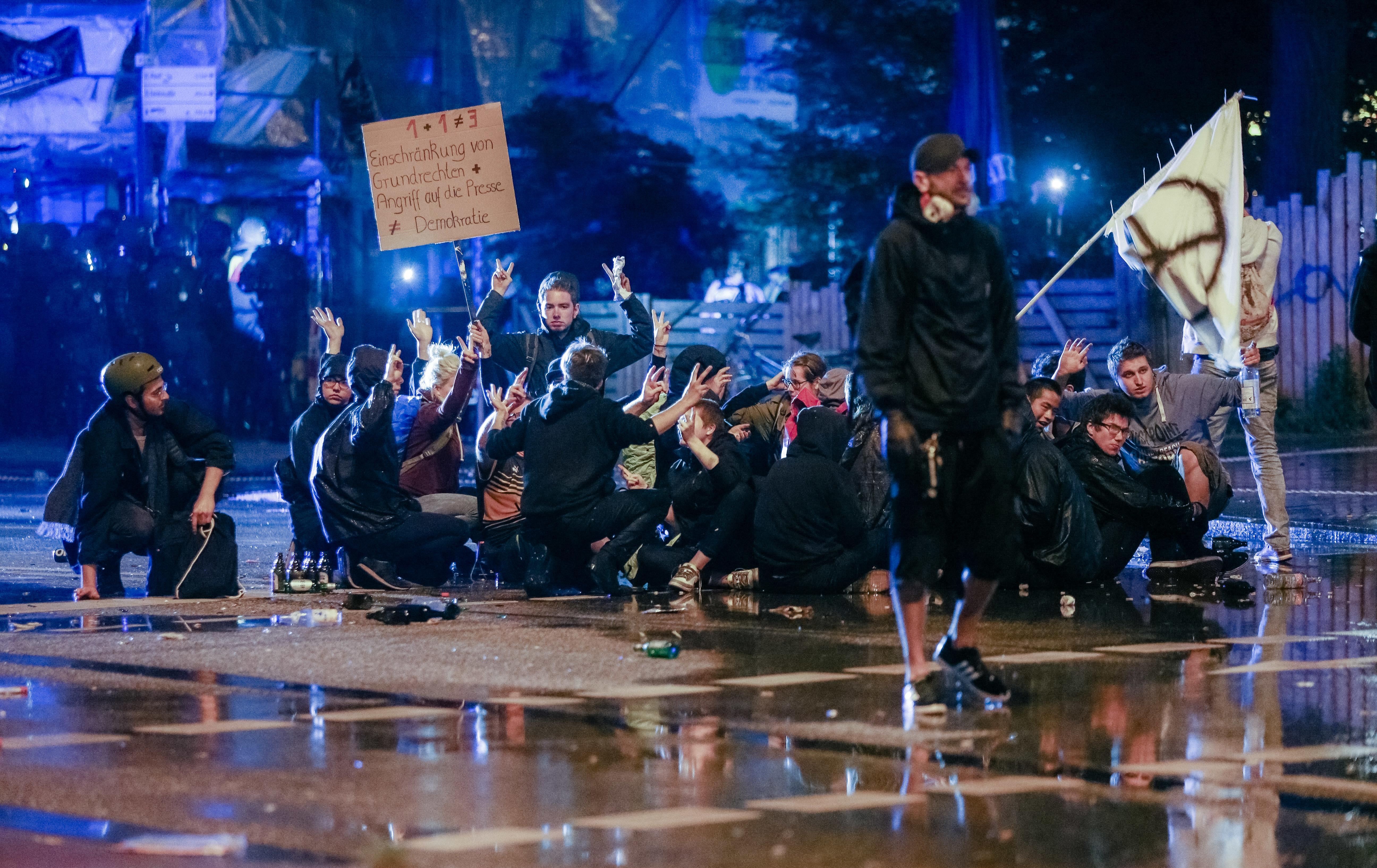 Demonstranten sitzen am 08.07.2017 in Hamburg in einer Straße im Schanzenviertel während die Polizei mit Wasserwerfern vorrückt. Am 07. und 08. Juli kamen in der Hansestadt die Regierungschefs der führenden Industrienationen zum G20-Gipfel zusammen. In der Nacht zum 08.07 eskalierten die Proteste im Schanzenviertel, die Polizei ging mit einem massiven Aufgebot gegen Randalierer vor. Foto: Markus Scholz/dpa +++(c) dpa - Bildfunk+++